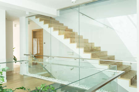 amenities: View of modern, bright corridor with minimalistic, wooden stairs with glazed handrail Stock Photo