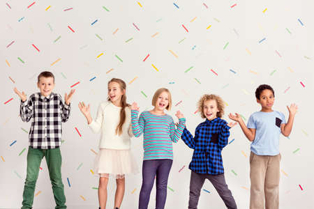 Sweet happy kids standing with their hands up
