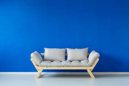 Simple blue living room with wooden bright sofa Stock Photo