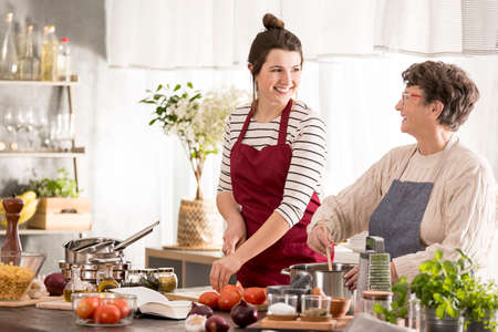 Happy, young woman cooking dinner with grandmother Stock Photo