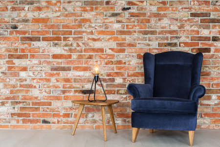 Wooden and velvet furniture set on a brick wall Stock Photo
