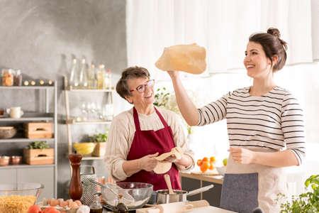 Gelukkige, jonge vrouw die pizzadeeg vormt terwijl het koken met oma