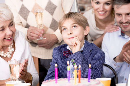 Boy making a wish at his birthday party and his family watching him