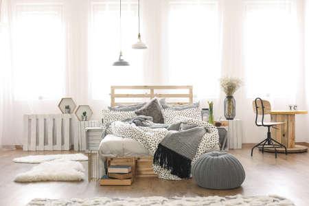 팔레트 침대와 케이블 스풀 테이블이있는 밝은 아파트