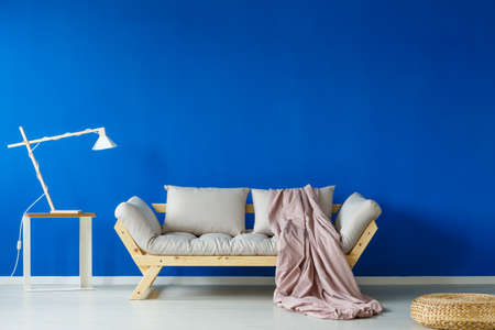 Pink plain blanket falling from white wooden couch