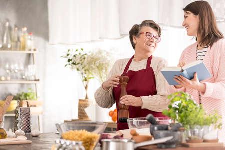 Jonge, gelukkige vrouw die grootmoeder recepten leest, samen koken Stockfoto - 81726215