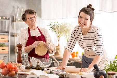 Gelukkig vrouwen rollend deeg voor deegwaren, die samen met oma koken