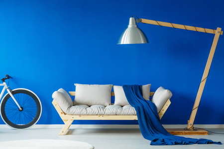 Messy bright wooden couch with blue blanket thrown on it
