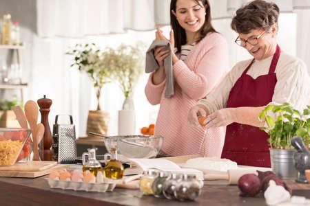 Vrouw koken verse pasta met haar gelukkige kleindochter
