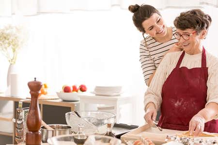 Granddaughter cooking with her happy grandma, having fun together Standard-Bild