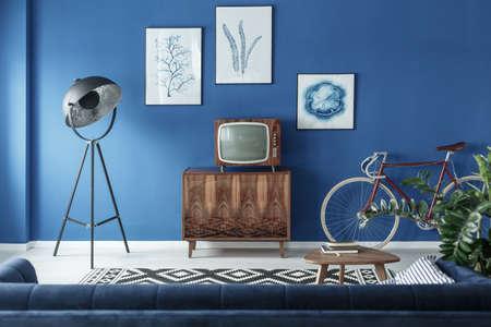 ビンテージ テレビ、自転車、モダンなリビング ルームでレトロなランプ