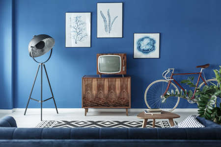 Vintage TV, bike and retro lamp in modern living room