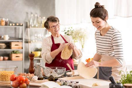 Grootmoeder die traditionele pizza bereidt met haar kleindochter
