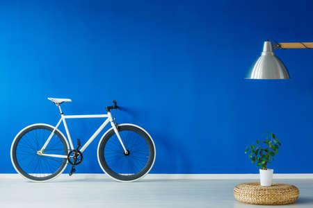 青のリビング ルームで黒と白の自転車に立って 写真素材