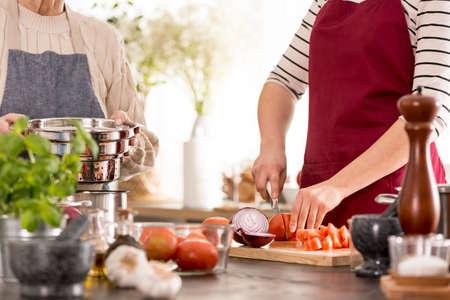 Vrouwen scherpe tomaten terwijl het voorbereiden van diner, omhoog sluiten Stockfoto