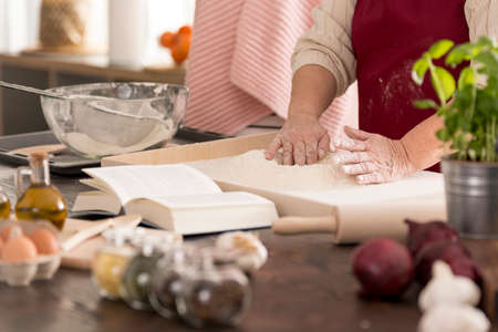 holiday spending: Woman preparing traditional dough for fresh pasta, close up Stock Photo