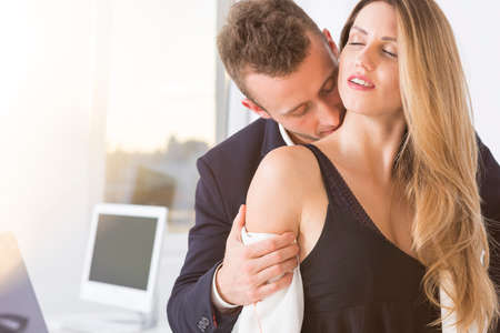 Young handsome man kissing young beautiful woman in the office Foto de archivo