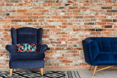 Armchair and sofa on a brick wall