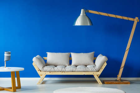 Two stylish lamps standing in a room with blue wall