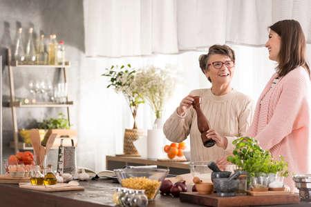 Gelukkige grootmoeder en haar kleindochter samen in keuken Stockfoto