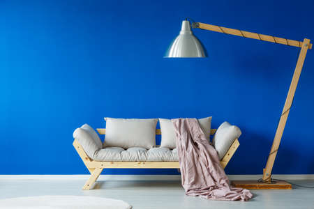 Blue living room with white carpet and oversize lamp