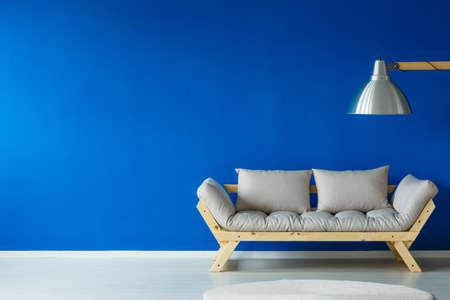 明るいソファ、壁の右側に立って