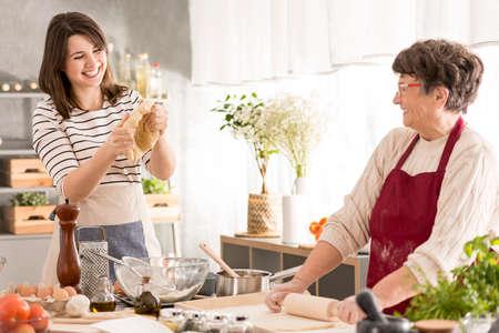 Grootmoeder en kleindochter hebben plezier terwijl ze samen koken