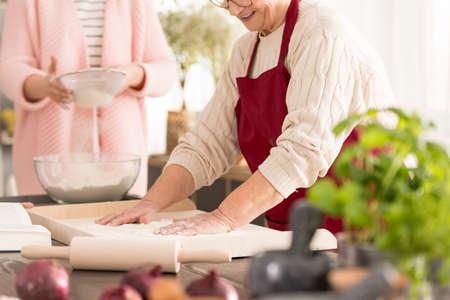 Gelukkige oma bereiden met kleindochter zelfgemaakte pasta Stockfoto - 81724896