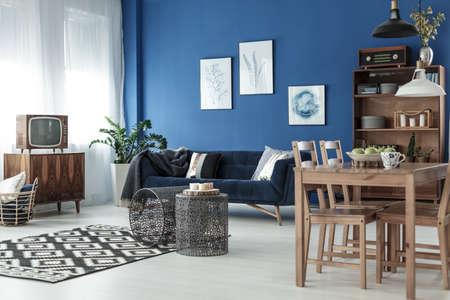 木製のダイニング テーブルとエレガントなアパートでビンテージのリビング ルーム