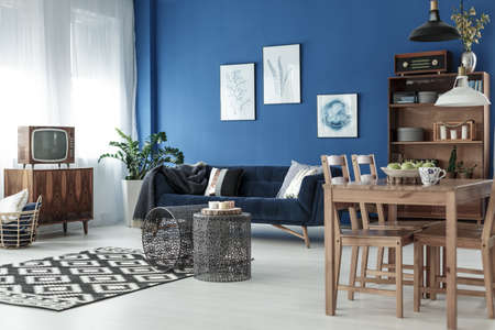 Wooden dining table and vintage living room in elegant apartment Standard-Bild