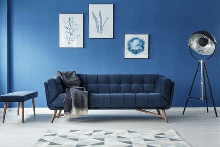 Elegant sofa, vintage lamp and footstool in stylish room Stockfoto