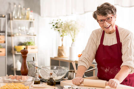 Happy senior woman rolling dough for pizza Stock Photo