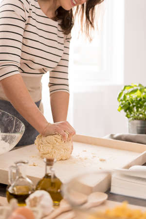 Young woman preparing dough for fresh pasta, close up