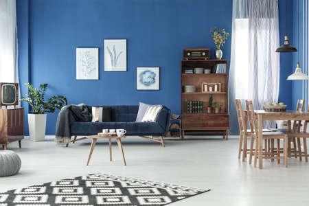 세련 된 아파트에 나무 식탁을 가진 레트로 거실 스톡 콘텐츠