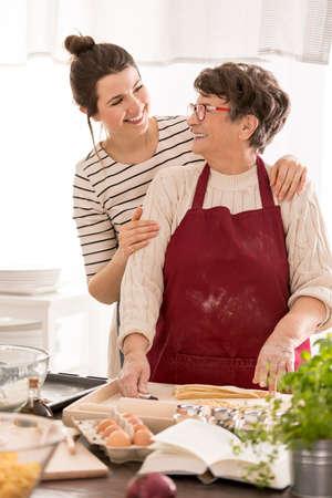 Vrouw omhelzen haar oma terwijl ze samen koken