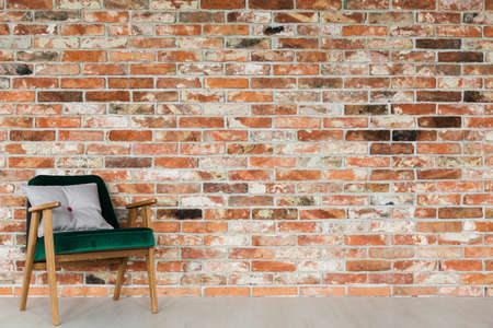 Green, velvet, vintage armchair on brick wall
