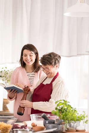 Kleindochter lezen aan haar gelukkige oma recepten uit het boek
