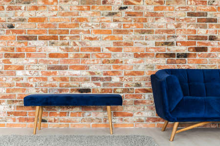 Minimal interior design with blue furniture and brick wall