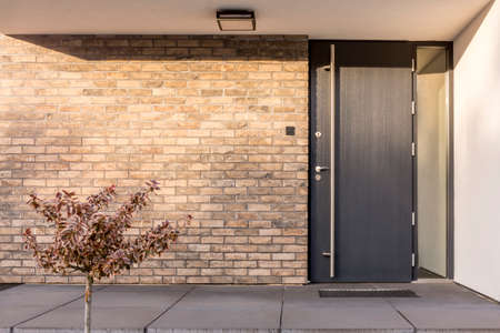 Minimalist clean red brick home exterior with black front door Banco de Imagens