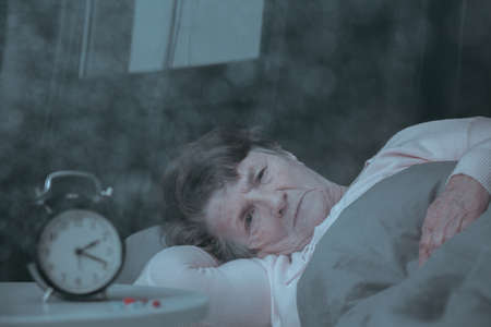 Sad older woman is lying in bed at night