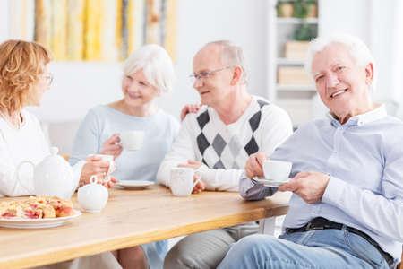 友達とコーヒーを飲みながら優雅な幸せな古い男