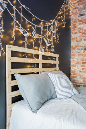 Creative pallet bed headboard with romantic fairy light decoration Stockfoto