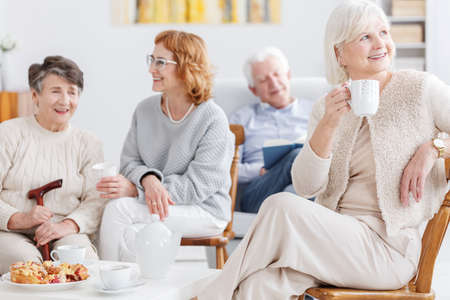 Elderly woman on her coffee time with friends in senior club Reklamní fotografie