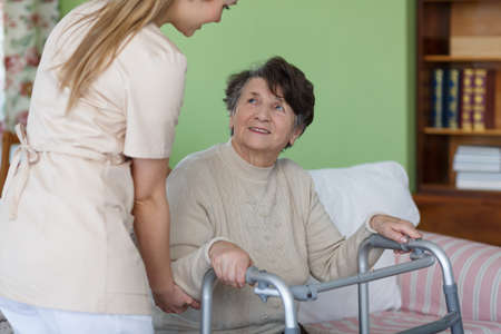 彼女の部屋での歩行で座っている高齢者の女性
