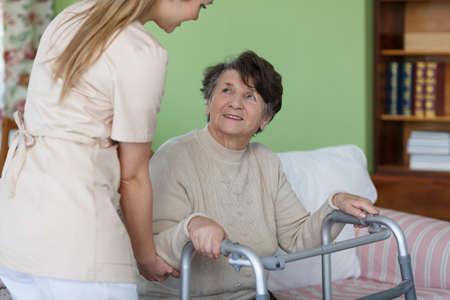 Oudere dame zat met een wandelaar in haar kamer Stockfoto