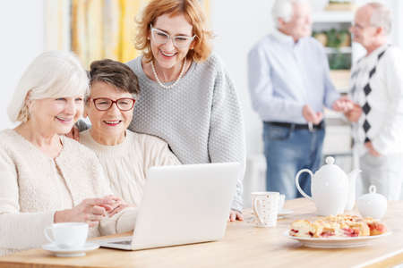 third age: Senior woman teaching her friends how to use laptop Stock Photo