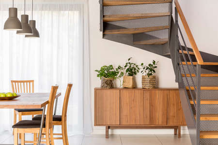 Dining room situated beside industrial wooden and metal staircase