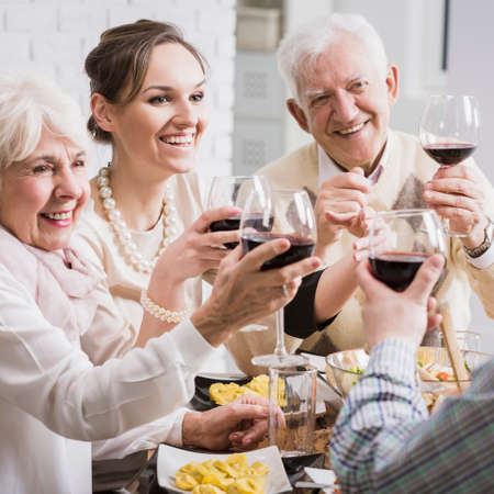 Senior parents and adult daughter toasting her promotion with red wine during elegant lunch Stock Photo