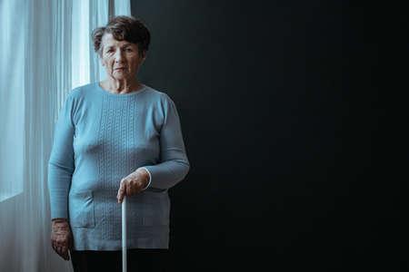 白い杖をついた立っている盲目の古い女性