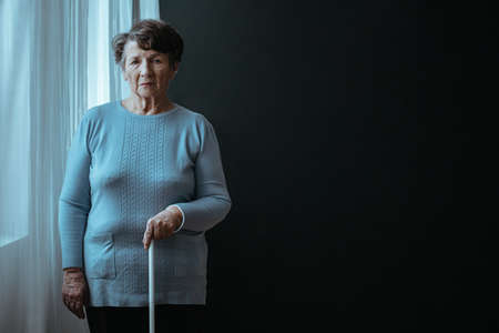Blind older lady standing with a white stick Stockfoto
